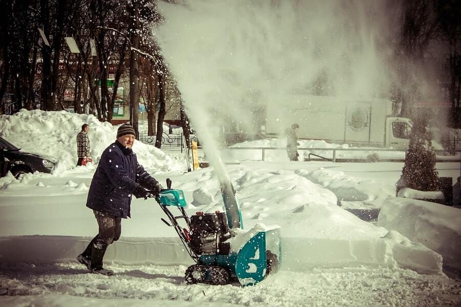 Man clearing up pathway with snow blower