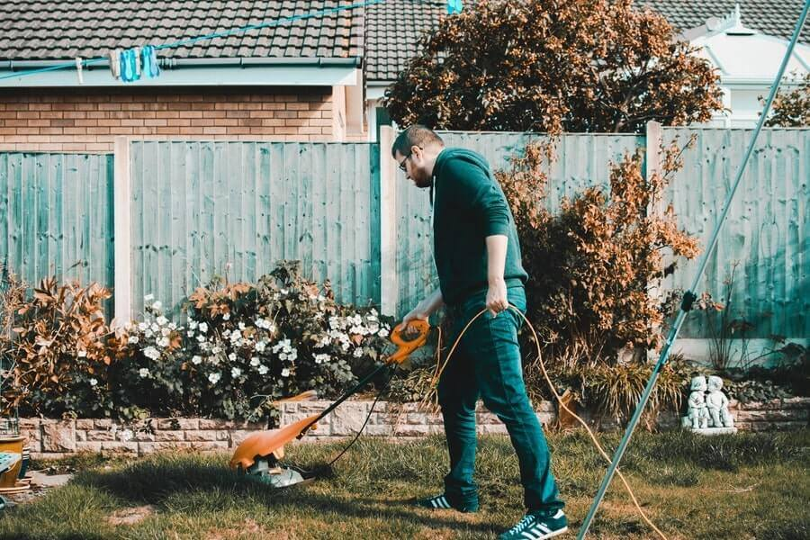 Man holding electric grass cutter