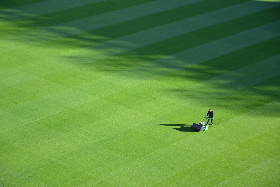 Man mowing football stadium grass