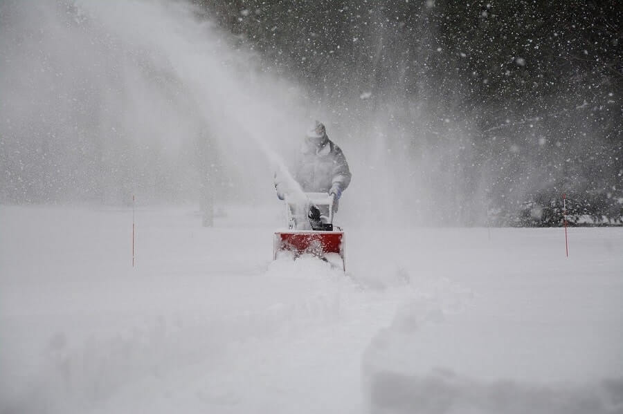 Man removing snow from pathway