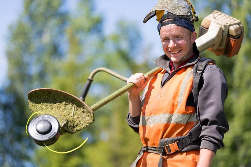 Man with protective gear and trimmer