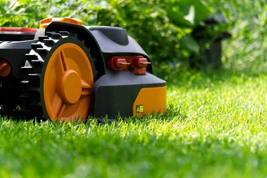 Orange mower on green grass