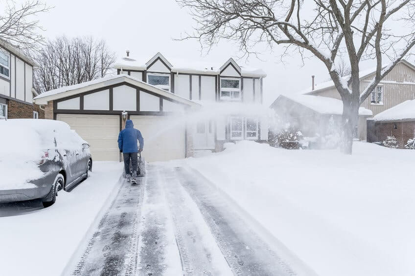 Man clearing a large driveway with snow blower