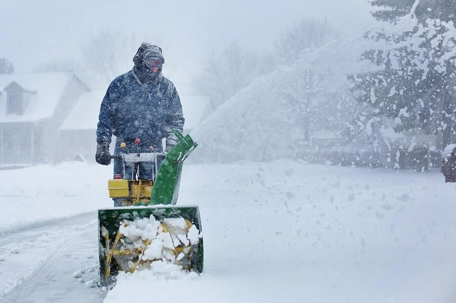 Man clearing snow while snowing