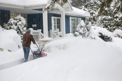 man using a snow thrower
