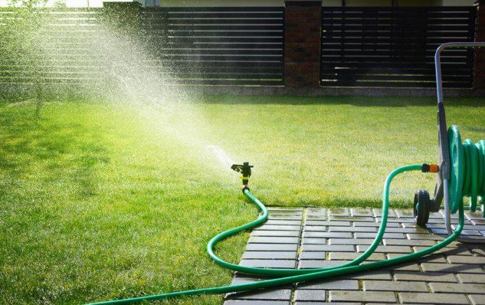 green garden hose sprinkler sprays water over grass