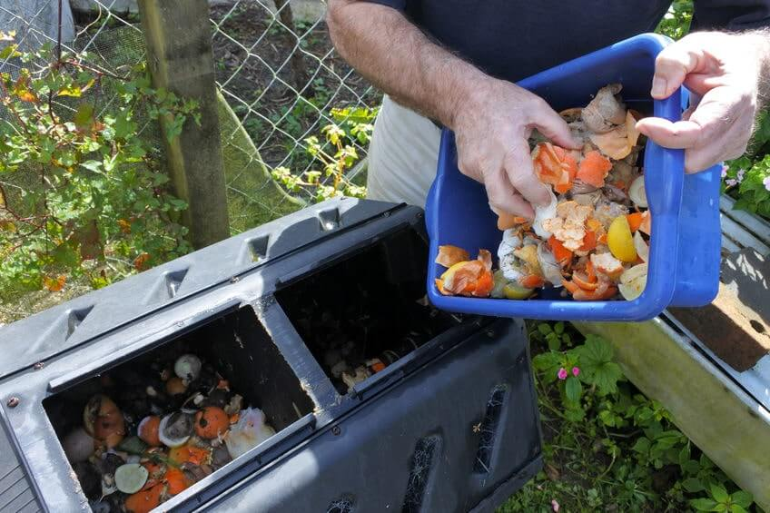 Man putting food scraps in compost bin
