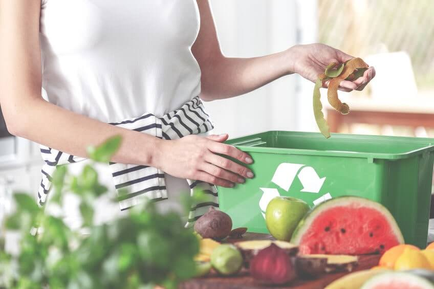 Woman disposing of food scraps in compost bin