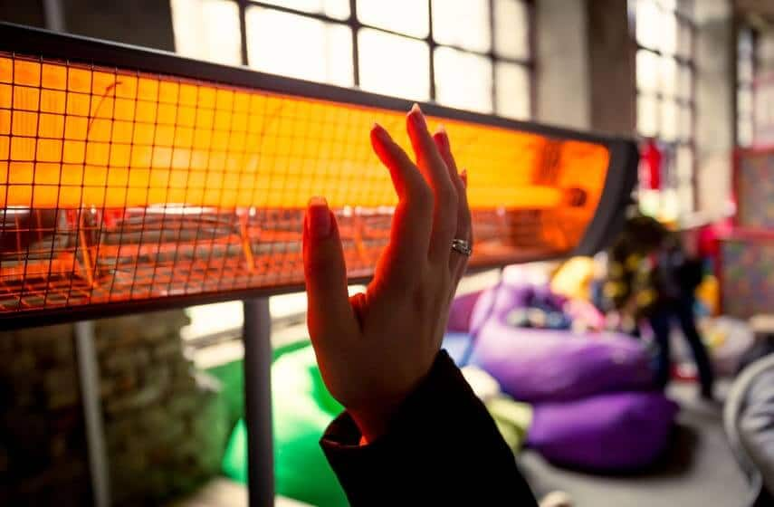 Woman heating hands by electric heater