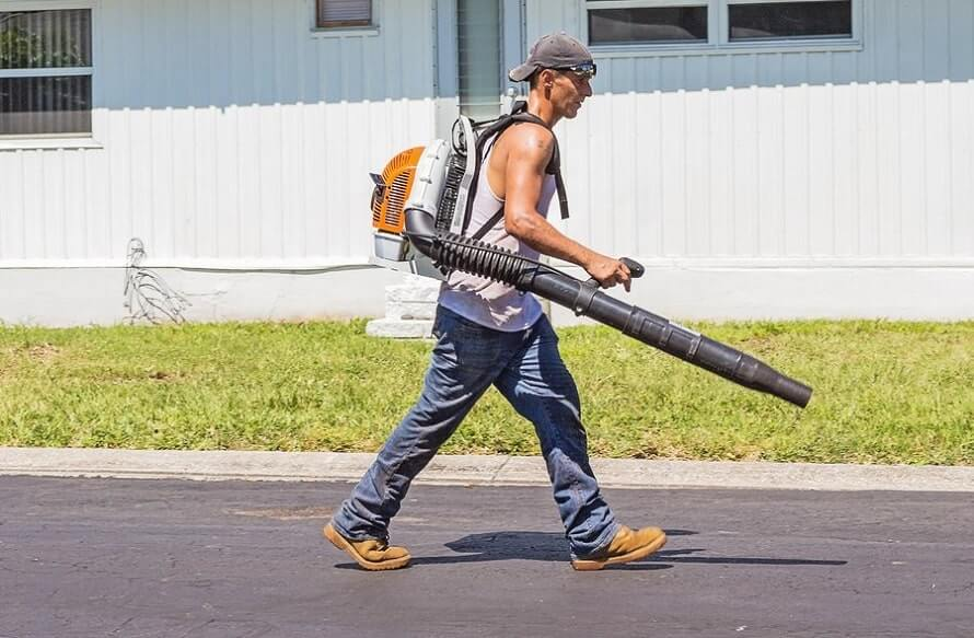 Man walking with backpack leaf blower on