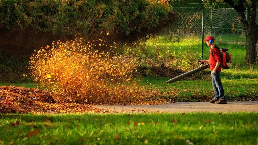 Man blowing big pile of leaves with backpack leaf blower