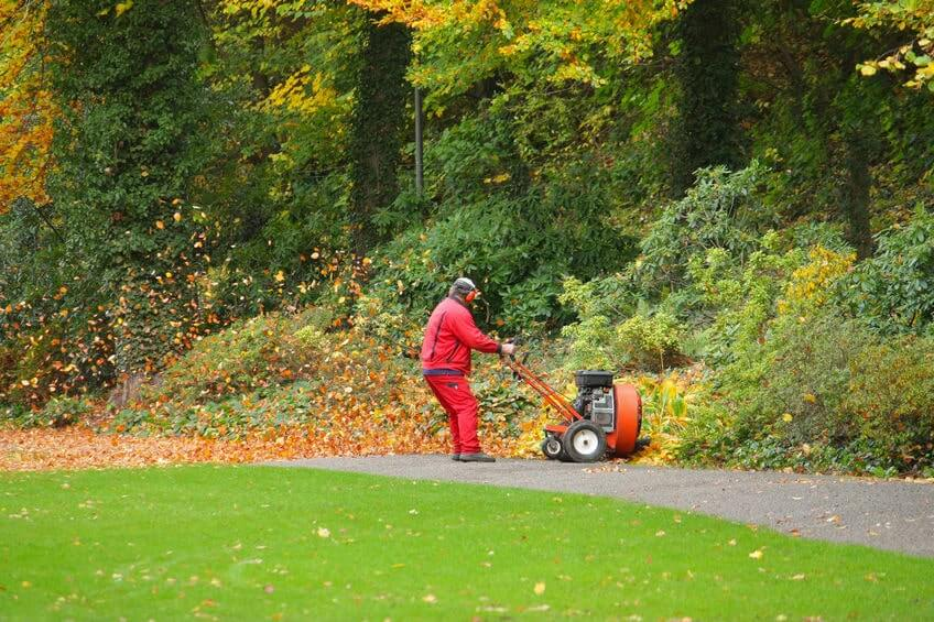 Man removing leaves with push leaf blower