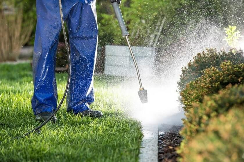 Person cleaning yard with pressure washer