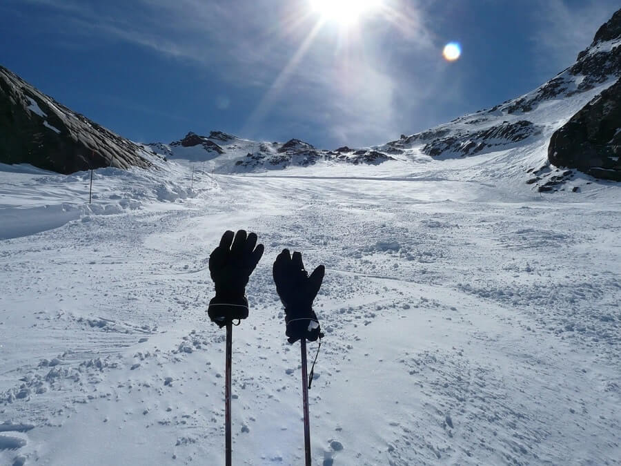 Gloves hung on two skiing poles