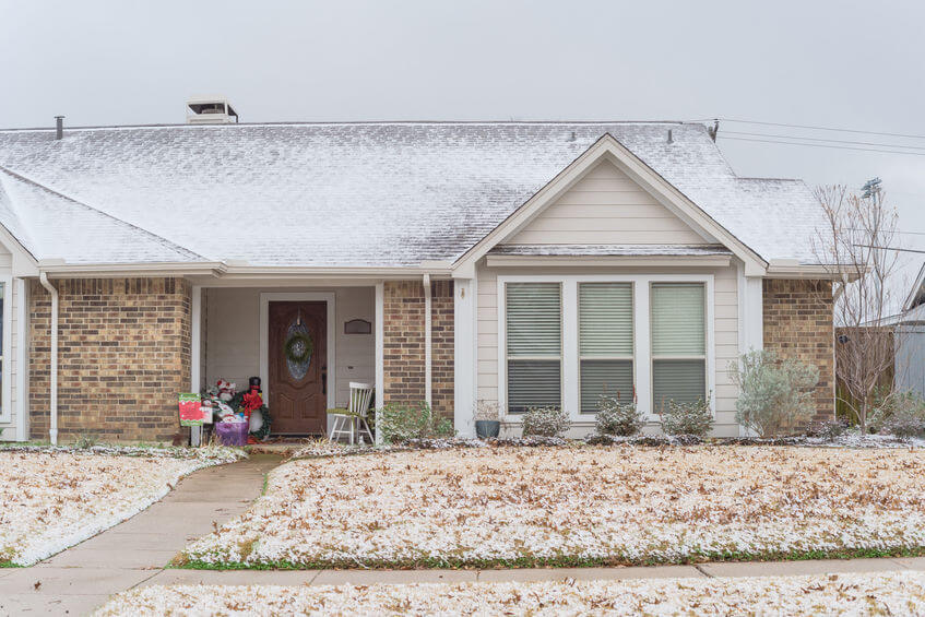 bungalow house with green lawn under winter snow