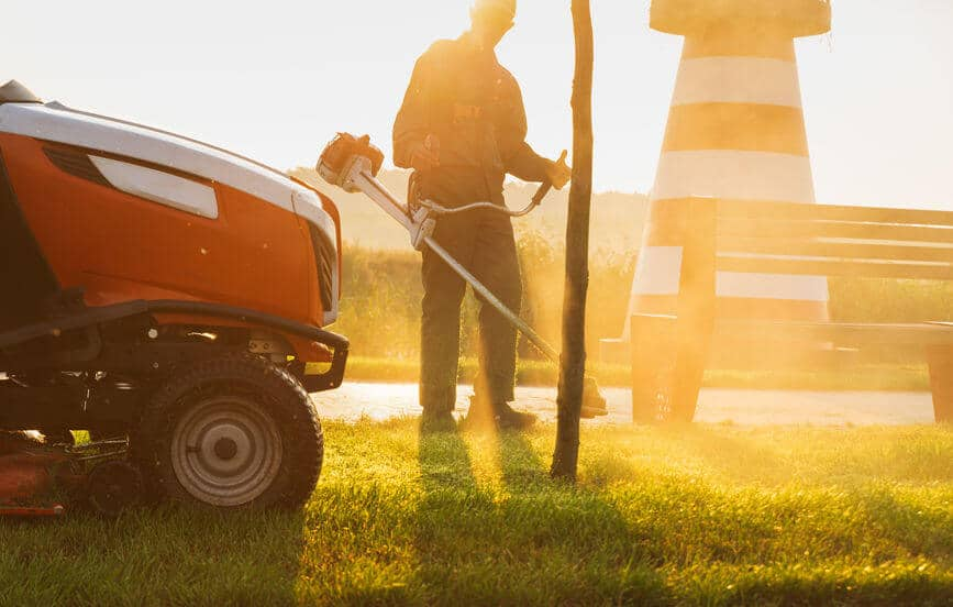 gardener mows the lawn with trimmer near to lawn mower tractor