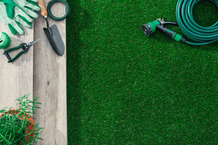 gardening and lawn care tools on a wooden table and lush grass
