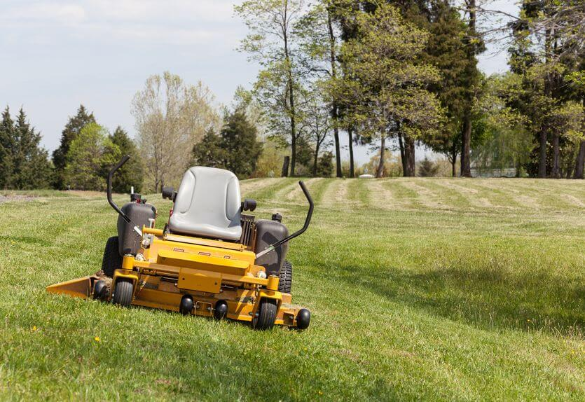 lawn with a yellow zero-turn lawn mower