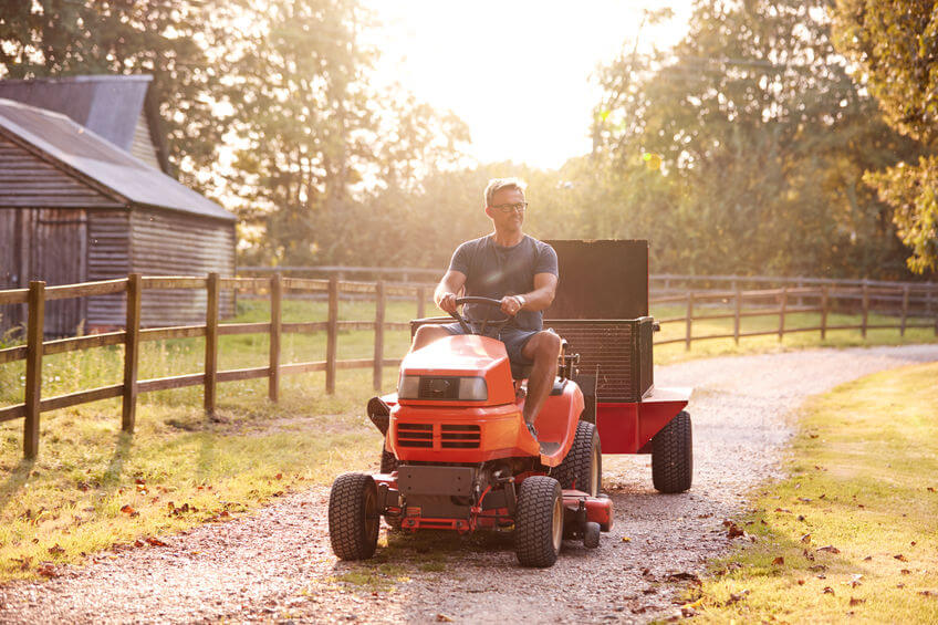 man driving ride on lawn mower with tow-behindy utility dump cart