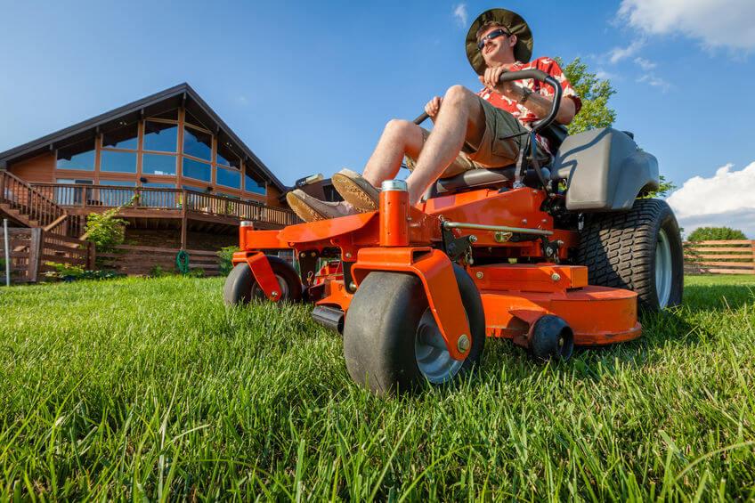 man working on red zero-turn lawnmower