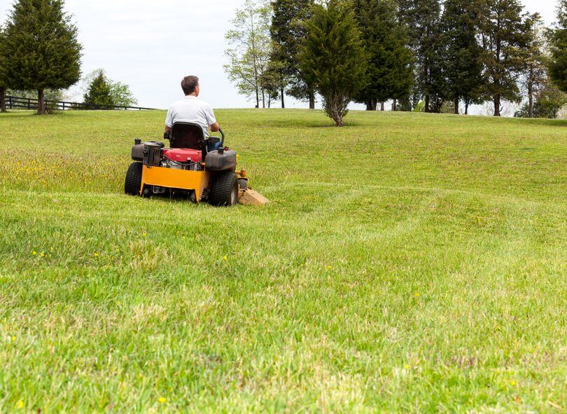 man working with a yellow zeru turn lawn mower