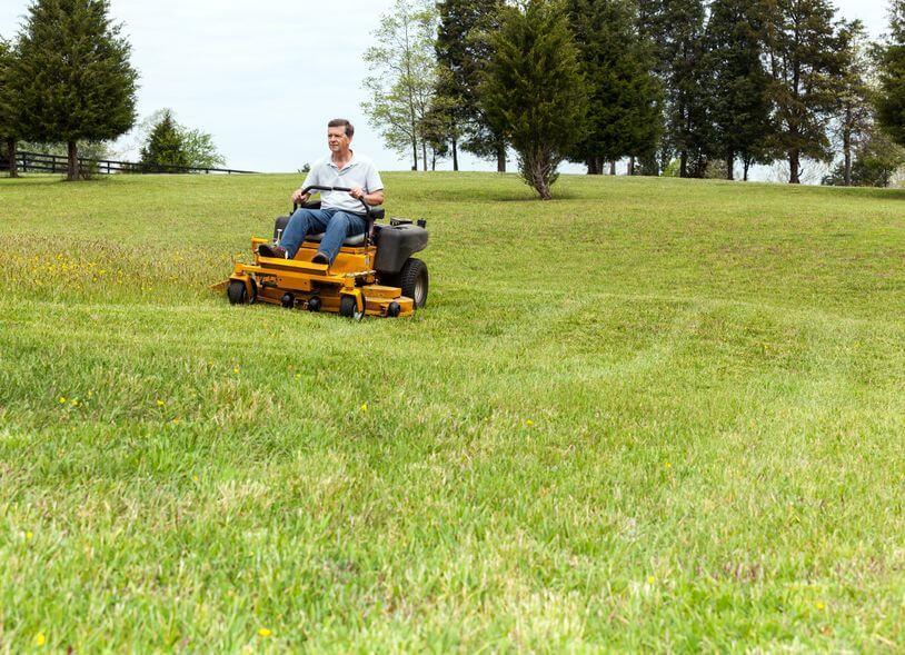 person using zero-turn lawnmower