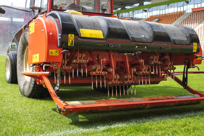 red tractor with tow behind aerator