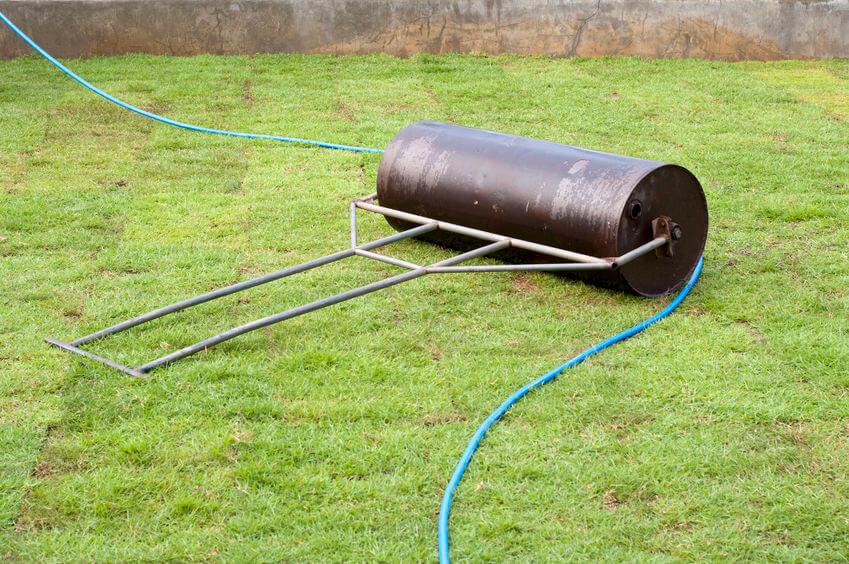 steel lawn roller on green lawn