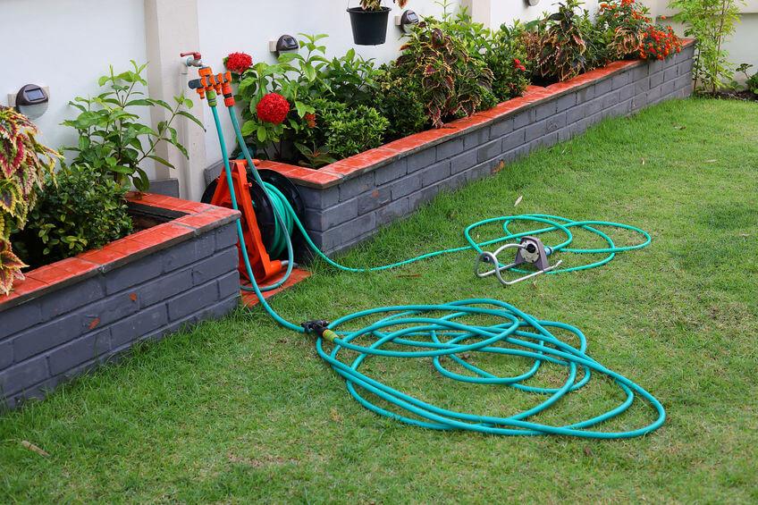 watering hose equipment in green grass of backyard