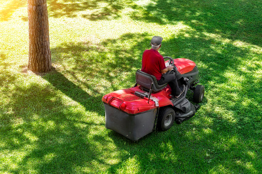 worker and red gas riding lawnmower with attached lawn bagger