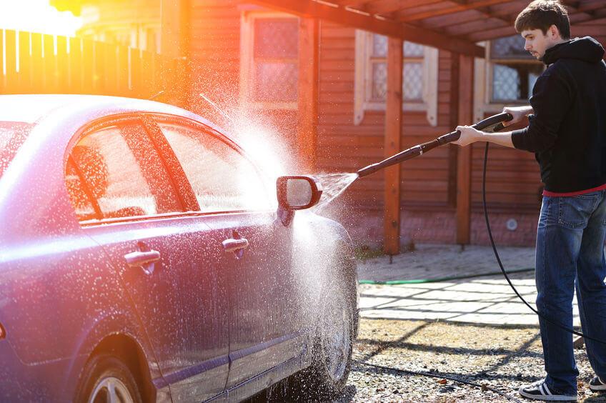 young man washing car in sunlight